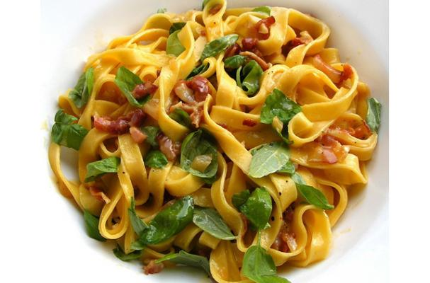 tagliatelle alla carbonara garnished with fresh basil